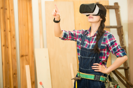 Artisan woodworker touch screen with in simulation virtual reality, carpenter standing and experience using a VR glasses device. mixed race asian chinese model. Imagens