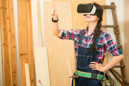 VR 가상 장치를 사용하여 시뮬레이션 가상 현실, 목수 및 경험을 가진 장인 woodworker 터치 스크린. 혼합 된 경주 아시아 중국 모델입니다.