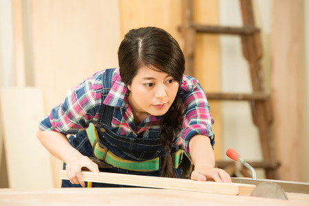 Skilled carpenter cutting a piece of wood in her woodwork workshop, using a circular saw. mixed race asian chinese model.