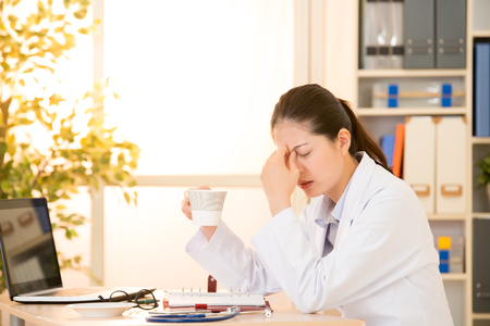 Tired and depressed doctor in medical office drinking coffee touch bridge of nose. mixed race asian chinese model. medical and healthcare concept. Stock Photo