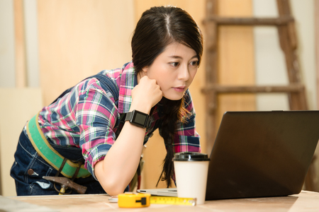 woman carpenter using laptop computer with smartwatch at workshop. mixed race asian chinese model. Stock Photo