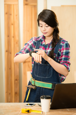 woman carpenter checking message on her smartwatch connecting with her computer near circular saw in a dusty workshop. mixed race asian chinese model.