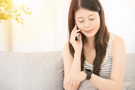 front view of beautiful woman using smartphone and smartwatch on the sofa. mixed race asian chinese model. Stock Photo