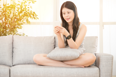 homeoffice: woman working from home using smartphone and smart watch. mixed race asian chinese model. Stock Photo