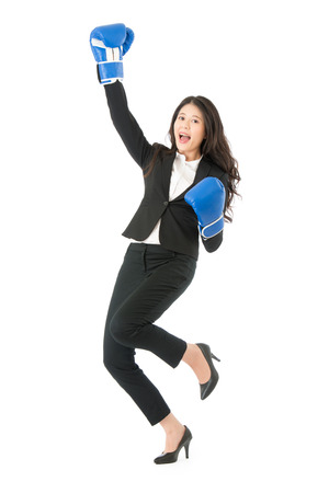 Winning business woman celebrating wearing boxing gloves and business suit. Winner and business success concept photo of young multiracial Asian businesswoman isolated on white background.