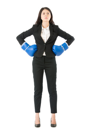 Businesswoman standing intimidating wearing boxing gloves ready for the competition. Strong business woman boss executive concept. Confident attitude by young mixed race asian model in suit. Stock Photo - 77623192