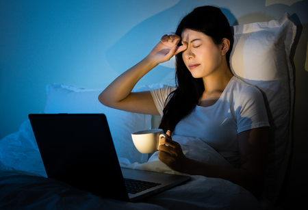 businesswoman rubbing eyes drinking coffee to working with computer sitting on bed at room. mixed race asian chinese model.