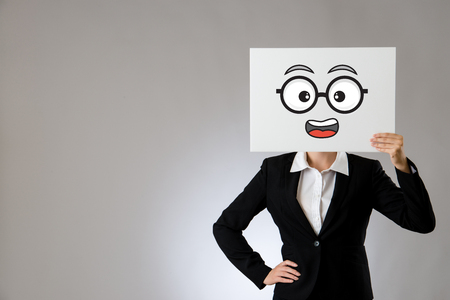 office lady boss holding blank white board with shocked face drawing. isolated on gray background. business office company concept.
