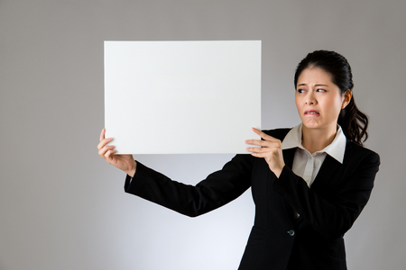 Banner sign woman holding blank empty paper billboard with copy space for text. Beautiful Asian woman looking blamed and scared.  isolated on gray background. mixed race asian chinese model.