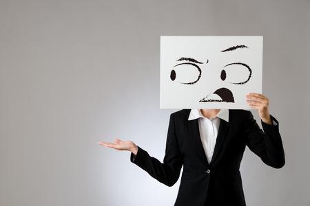 geschokt gezicht tekenen op witte lege bord houden door mooie zakenvrouw en tonen presenteert handgebaar. geïsoleerd op grijze achtergrond. zakelijke kantoor bedrijf concept.