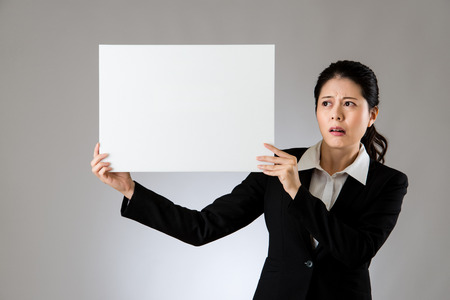 Scared business woman holding white sign board with sad face expression. isolated on gray background. mixed race asian chinese model.