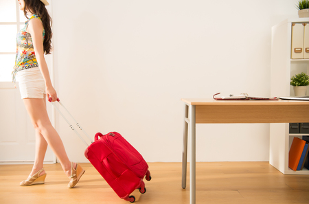 business woman carrying her suitcase ready to go for long vacation and escape the work for relaxing. mixed race asian chinese model. Фото со стока