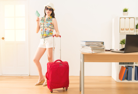 Successful young businesswoman packing everything ready in the office time to leave work for holiday. vacations and travel concept. mixed race asian chinese model.