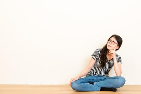 混血の質問を感じる混乱を考えるアジア女。空白のコピー領域の背景の白い壁に木の床の上に座って t シャツ トップを着ています。 写真素材