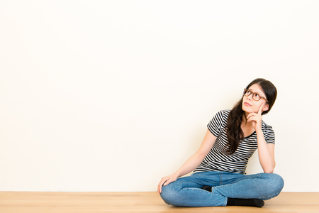 mixed race asian woman thinking question feel confusion. wearing t-shirt top sitting on wooden floor over blank copy space white wall background.
