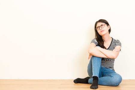 Mujer confundida confundido estudiante pensando y soñando con ropa casual sentada en el piso de madera sobre fondo blanco pared de espacio de copia en blanco . Foto de archivo - 77767258