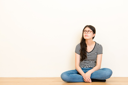 Thoughtful young girl thinks worry about her future and dreaming sitting on wooden floor over blank copy space white wall background.