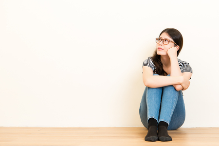Portrait of a beautiful woman thinking and looking worried sitting on wooden floor. Young girl looking up at blank white wall background. Stock Photo