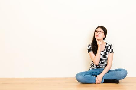 빈 복사본 공간 흰 벽 배경 위에 앉아 티셔츠 탑을 입고 질문에 [NULL]에 대해 생각하는 혼합 된 인종 아시아 여자 닫습니다.