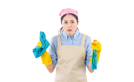 Tired attractive young woman in yellow gloves and apron standing and feel sleepy after cleaning job. isolated on white background. housework and household concept.