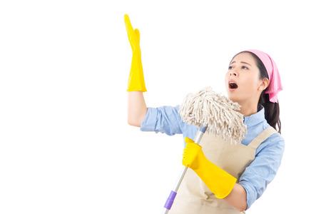 混血アジア クリーニング女性春の大掃除中に楽しんでいます。面白い女性に向かって歌いほうきにゴム手袋をはめて掃除します。白い背景上に分離