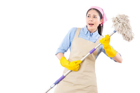 mixed race cleaning woman happy excited during spring cleaning. Funny energetic beautiful girl with cleaning broom playing air guitar isolated on white background. housework and household concept.