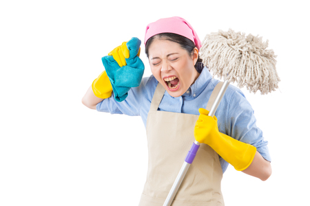yelling young crazy angry housewife having a calamity at home reacting in shock with holding mop and rag. isolated on white background. housework and household concept. Stock Photo