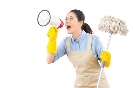 De schoonmakende vloer van de vrouwenwas met zwabber en holdings luide spreker die iedereen roepen tijdens de lente het schoonmaken. Multiculturele Chinese Aziatische huisvrouw die op wit wordt geïsoleerd. Stockfoto