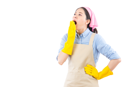 sleepy young cleaning house woman with wide open mouth yawning eyes closed looking bored. isolated on white background. housework and household health care concept. Stock Photo