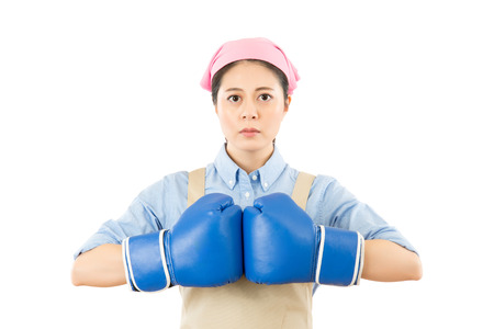 aggressive young mixed race Chinese Asian woman punching blue boxing gloves together. isolated on white background. housework and household idea concept.
