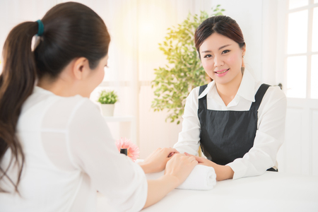 confidence gorgeous female asian salon business owner sitting in front of her nail salon while a customer gets a manicure Stock Photo