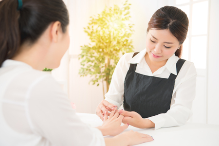verify: The manicurist holds hands of the client in beauty salon on desktop for manicure with nail polishes, creams and lighting instruments. beauty and fashion concept.