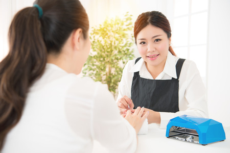 Portrait of an attractive nail salon worker giving a manicure to one of her regular customers using portable uv light dryer and manicure related objects. beauty and fashion concept. Stock Photo