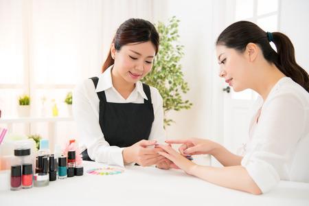 プロのネイル アーチストと彼女のクライアントは、ディスカッション、彼女が行うサロンにおけるサービスの爪美容今日および提示のカラー パレッ