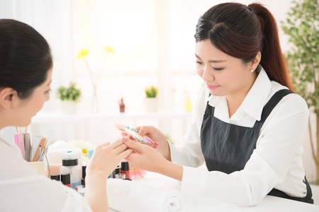 beauty asian chinese manicurist showing color shellac nail polish for her customer to selects manicure letter of nail services in beauty salon.