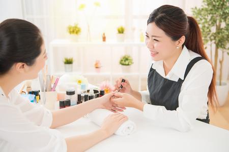 De profielmening van vrij gemengde jonge Aziatische vrouwen geniet van manicure en sprekend met haar manicure bij echte salon spa achtergrond. schoonheid en mode concept. Stockfoto