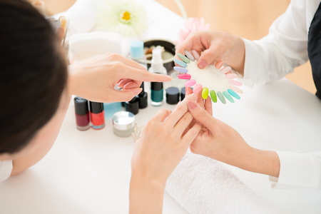 Top view of asian chinese woman selects manicure color shellac nail polish. Nail technician shows the color palette of nail services in beauty salon.