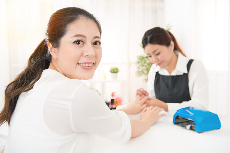 happy mixed race asian chinese woman enjoy doing her resting relax manicure by professional manicurist using portable uv light dryer in a beauty salon.