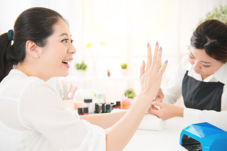 excited happy mixed race asian chinese woman enjoy love her new done manicure by a manicurist using portable uv light dryer and manicure related objects in a beauty salon. Stock Photo