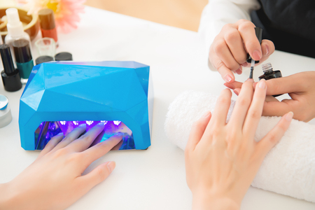 Female hands using portable uv light dryer and manicure related objects in spa salon background. beauty and fashion concept. Stok Fotoğraf