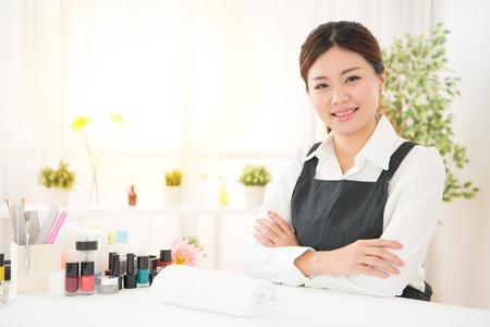 Propriétaire de salon de beauté asiatiques femme magnifique salon assis devant la caméra prêt à montrer son manucure professionnel Banque d'images - 77939330