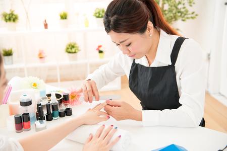 アジア中国女性の手は、マニキュアを受信します。爪のファイリング、ネイルサロン、スパ ・ トリートメントの選択と集中をクローズ アップ。美 写真素材