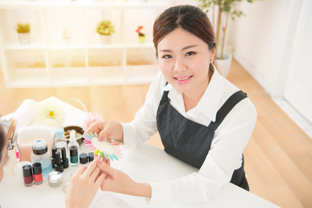 high angle above view of asian mixed race girl customer chooses the color of testers nail polish for manicure services in beauty salon.