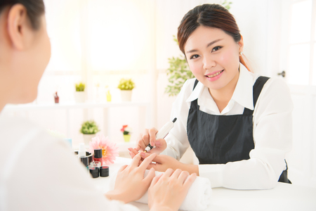 Close up shot of Manicurist is applying electric nail file drill to manicure on female fingers at real salon spa background. beauty and fashion concept.