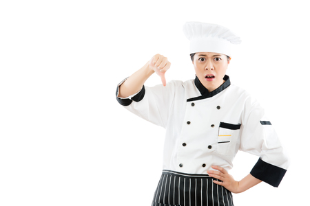 mixed race asian woman chef dislike and showing thumb down hand signal gesture. isolated on white background. profession and industry job concept. Stock Photo