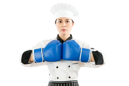 beautiful cooking woman wearing boxing gloves ready for the competition showing strong body standing intimidating food problem executive concept with blank area over copyspace white wall background.