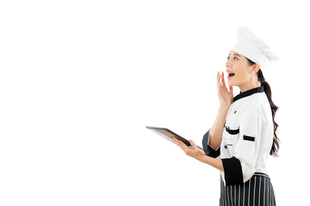 happy chef opening electronic menu online with digital tablet and projecting in blank area surprisingly watching copyspace standing on white wall background.