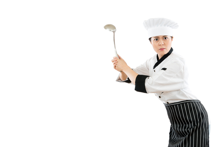 slim of the female chef holding a stainless steel spoon tool showing a golf posing and gestures standing on a white background angry expression with blank copyspace.