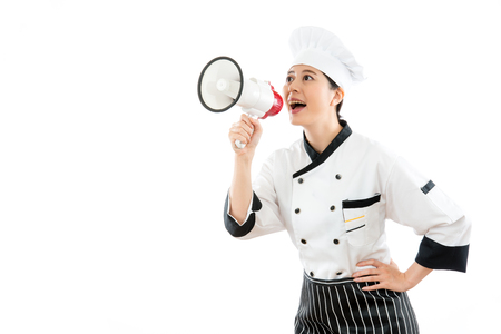 peddle: pretty chef speaking with the loud megaphone and publicity restaurant news information standing on the white wall background with blank area over copyspace for content.