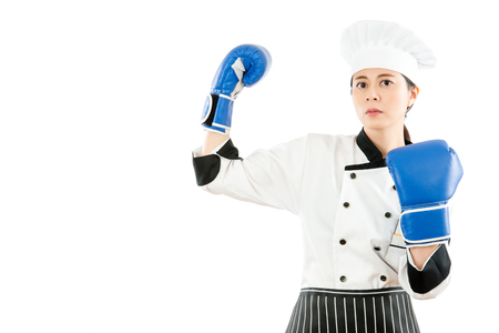 powerful strong pretty cooking woman arm up showing muscle with blue boxing gloves isolated on the white background for kitchen work and restaurant concept over copyspace. Stock Photo